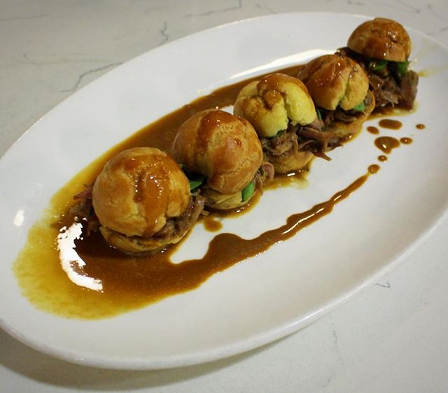 These are our Duck confit sliders with aged sherry dressing and profiterole. Available as a starter on our nightly dinner menu, a wonderful beginning to a night of great food.  Duck confit is a French dish made with the whole duck. The confit is prepared in a centuries-old process of preservation that consists of salt curing a piece of meat and then cooking it in its own fat.  Thisleads to a succulent tender meat.  #topchef #seattleats #confit #yum #food52 #bonappetit #diningout #dinner #french #foodeducation