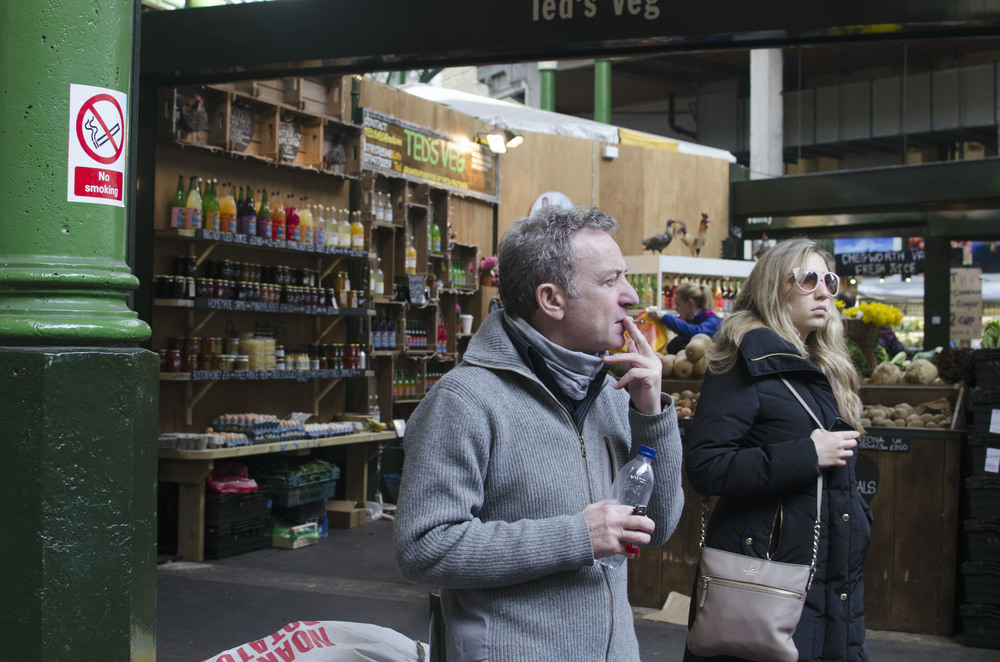 "A man smoking in front of a ""No Smoking"" sign at Borough Market."