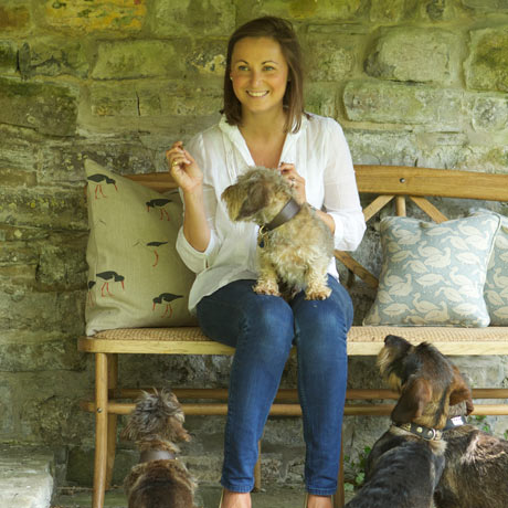 Emily Bond sitting on a bench surrounded by her cushions and her dogs