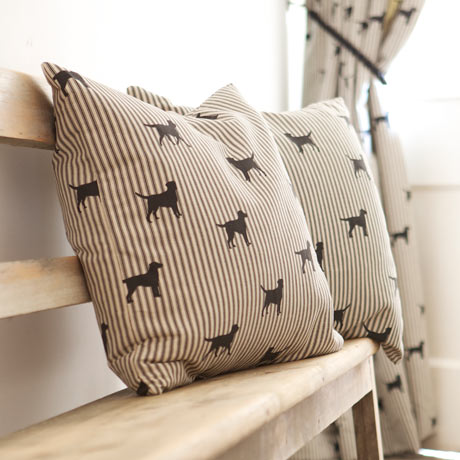 Two striped Emily Bond cushions with dogs on them on a bench with a matching curtain in the background
