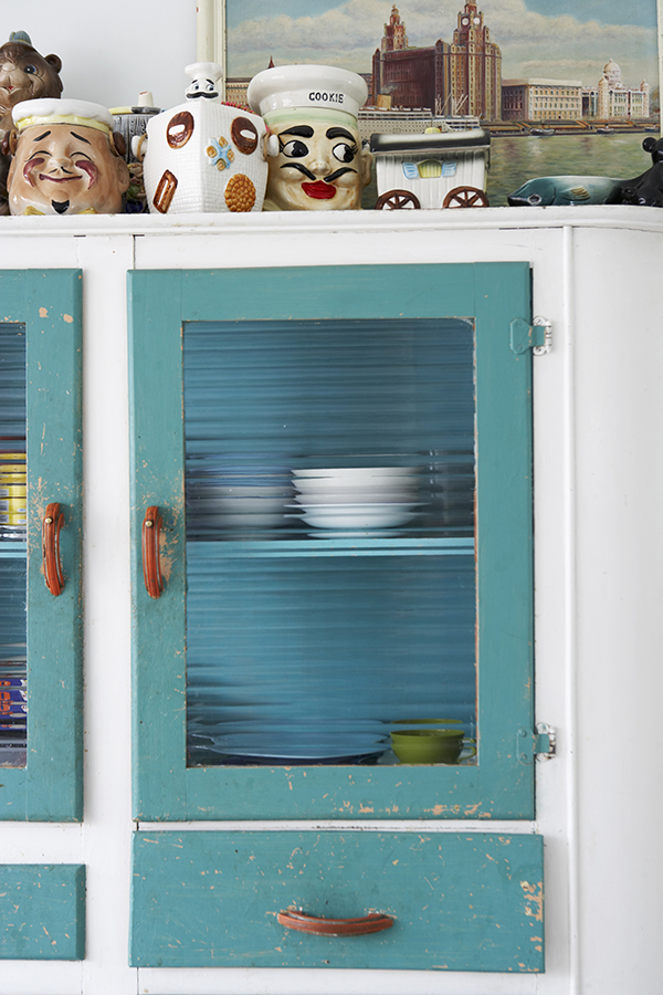The original ribbed glass door panels and worn paintwork testify to this storage unit's date and authenticity, while the top is used to display a collection of humorous and vintage ceramics.