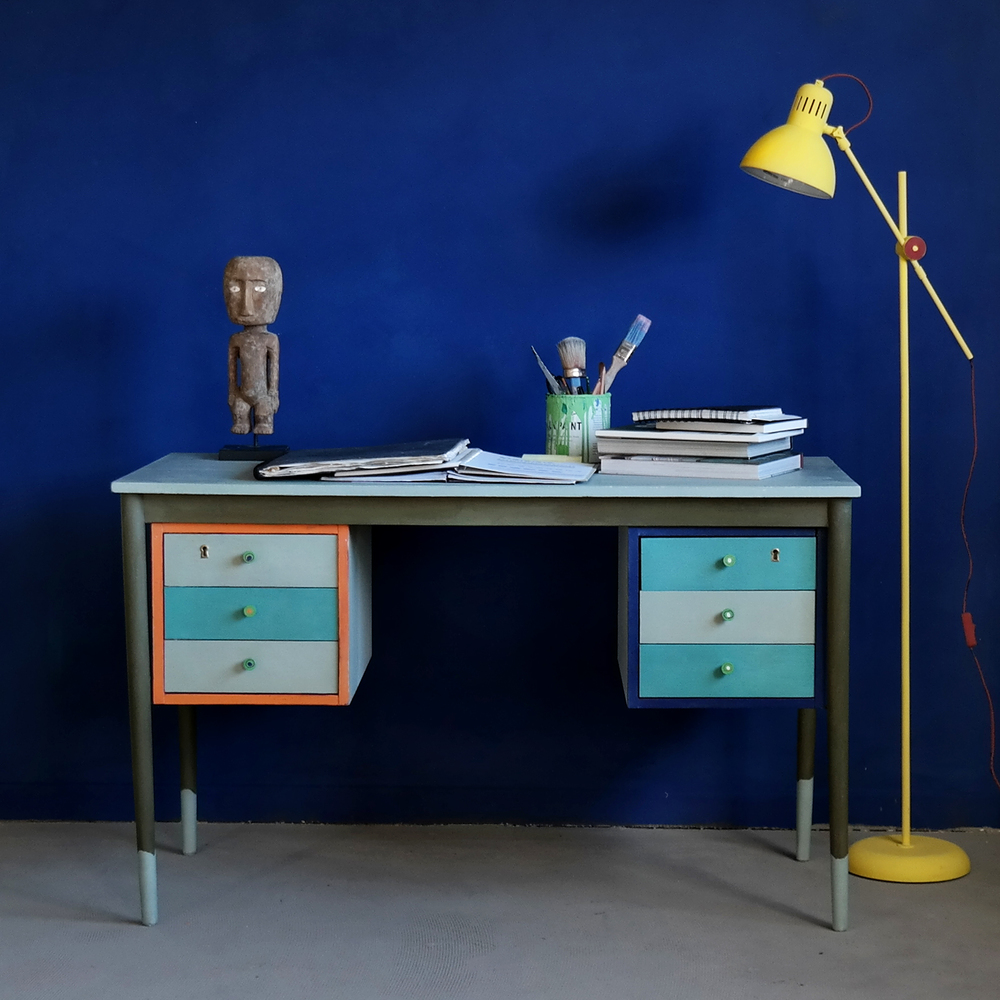 This is Annie Sloan's own desk – a 1950s Danish-style desk painted with Duck Egg Blue lightened with Pure on the desk top. This colour was followed through on some of the drawers with a contrast of Provence on the others. The legs were painted in Olive with feet in Duck Egg Blue. To create a truly Mid-Century asymmetrical look, Annie used a hot colour - Barcelona Orange - to frame the drawers on one side, and a cool colour - Napoleonic Blue - on the other. The door knobs were all painted in Antibes Green with contrasting dots of colour in the centres.  Clear Soft Wax was used to seal the piece.