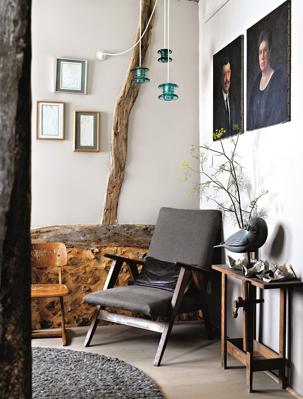 In a corner bound by beams, a small child's chair and an armchair from the 1950s. The hanging lights are electric glass isolators, making a contemporary mobile. On the wall, portraits of Julie's family and ink drawings by Alain Bonnefoit.
