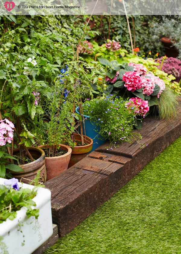 Reclaimed railway sleepers add a rustic touch to this city garden. If creating a similar look at home, bear in mind that reclaimed sleepers sometimes contain metal inserts – if you wish to cut some to size, it's best to purchase new ones to ensure you get a clean cut.