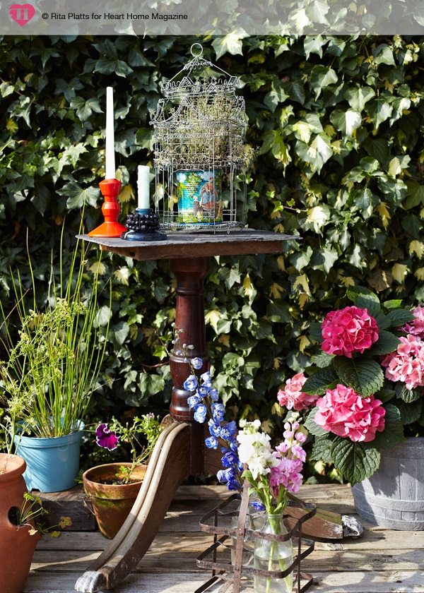 Lots of clever tricks have been used to add height within this garden: here, a discarded table leg, found on the street outside, has been topped with a slate roof tile to create a quirky plant stand.