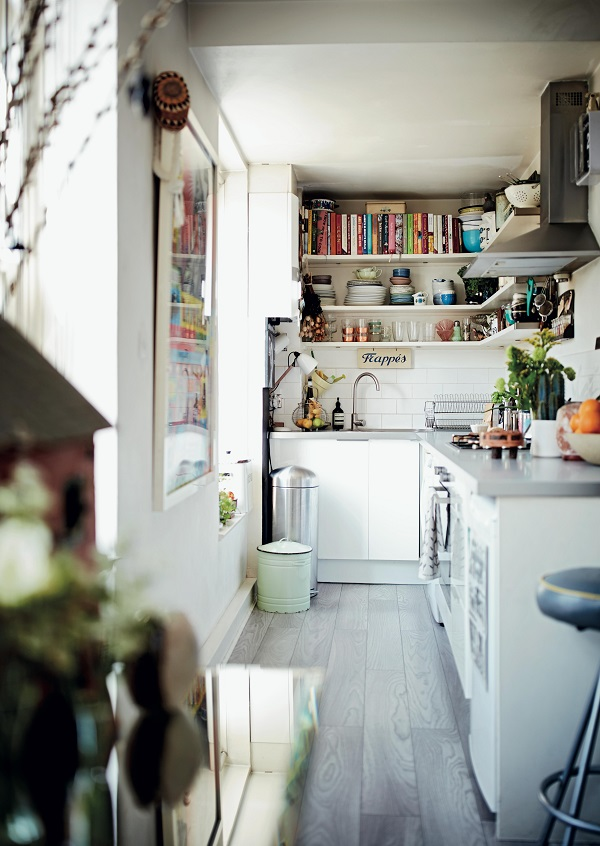 In the small galley kitchen just off the living room, storage is limited. Shelves are organised into cookbooks, pots/pans, dinnerware and glassware. A large framed poster hangs on the wall, adding further to the personality of the home.