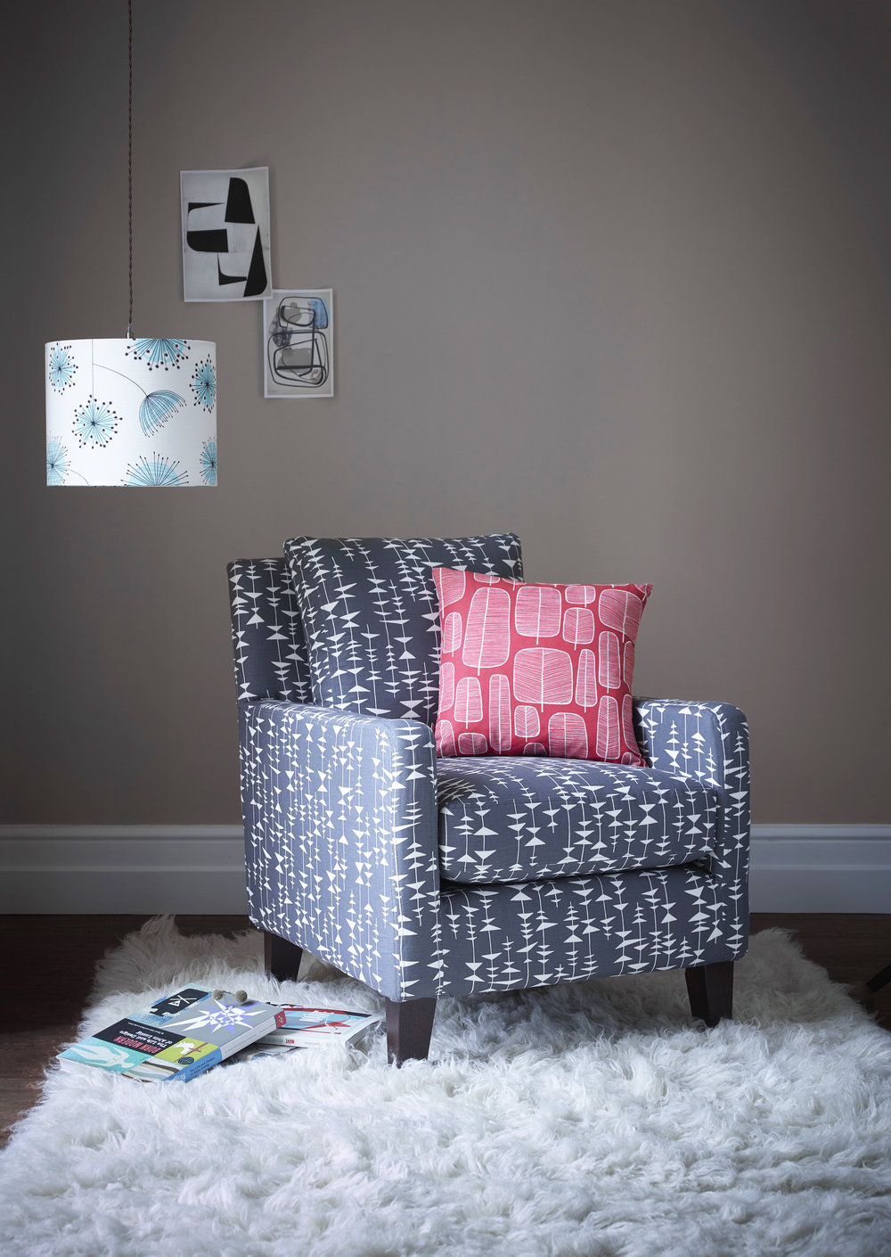 "Alfie Chair in Ditto Liquorice Fabric £1049, 17"" Scatter in Little Trees Chilli Fabric £59."