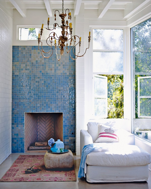 Small sky blue mosaic tiles give a mother-of-pearl shimmer as they catch the light above a simple fireplace. Tiling is a good way of adding colour to kitchens, living room and bedroom fireplaces and bathrooms.