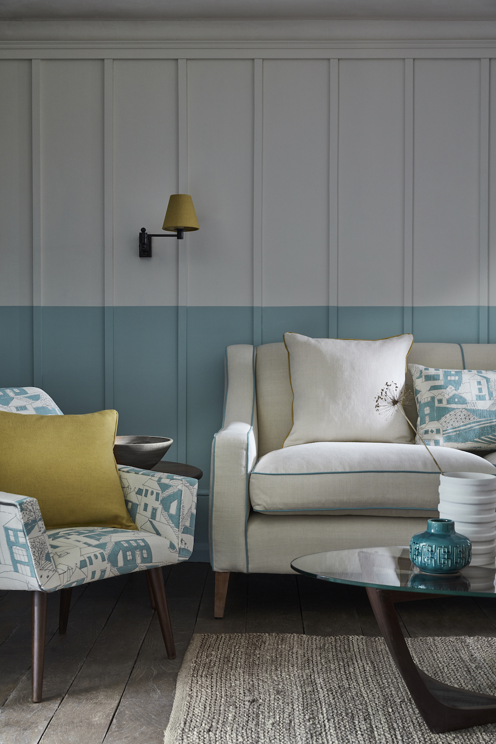 CHAIR: By the Sea Teal, Charcoal SEA-20-38 £52/mtr, CUSHION (on chair): Self piped and zipped Plain Linen Saffron PLAIN-52 £48/mtr, CHEDWORTH SOFA: Plain Linen Cream PLAIN-3 £48/mtr piped in Plain Linen Teal PLAIN-20 £48/mtr, CUSHION (left): Plain Linen Cream PLAIN-3 £48/mtr piped in Plain Linen Saffron PLAIN-52 £48/mtr, CUSHION (right): Rectangular self piped and zipped By the Sea Teal, Charcoal SEA-20-38 £52/mtr, LAMPSHADE: Plain Linen Saffron PLAIN-52 £48/mtr, LIGHT FITTING: Hanson Wall light in Matt Black by Jim Lawrence £87.20, RUG: Handmade Looped by Scumble Goosie £49 each, PAINT: Main wall Linen Wash 33 and Brighton 203 by Little Greene Paint Company £42 per 2.5 ltr.