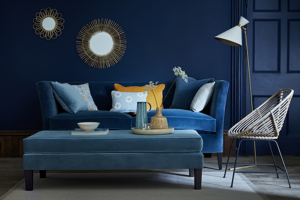 CIRENCESTER SOFA: Tarn Velvet VELVET-78 £58/mtr; FOOTSTOOL: Lake Blue Velvet VELVET-77 £58/mtr; CUSHION (left front): Self piped and zipped Lake Blue Velvet VELVET-77 £58/mtr; CUSHION (left back): Self piped and zipped Pie in the Sky Speedwell, Straw PD-32-9 £49.50/mtr; CUSHION (middle front): Self piped and zipped Four Seasons Speedwell, Denim, Straw FR-32-6-9 £49.50/mtr; CUSHION (middle back): Self piped and zipped Honey Velvet VELVET-72 £58/mtr; CUSHION (right back): Self piped and zipped Tarn Velvet VELVET-78 £58/mtr; CUSHION (right front): Self piped and zipped Cow Parsley Duck Egg, Cornflower CP-8-16 £49.50/mtr; RUG: Stripe and Dash Smoke, Cornflower RSD-30-16 £390; PAINT: Royal Navy 257 by Little Green Paint Company £42 per 2.5 ltr