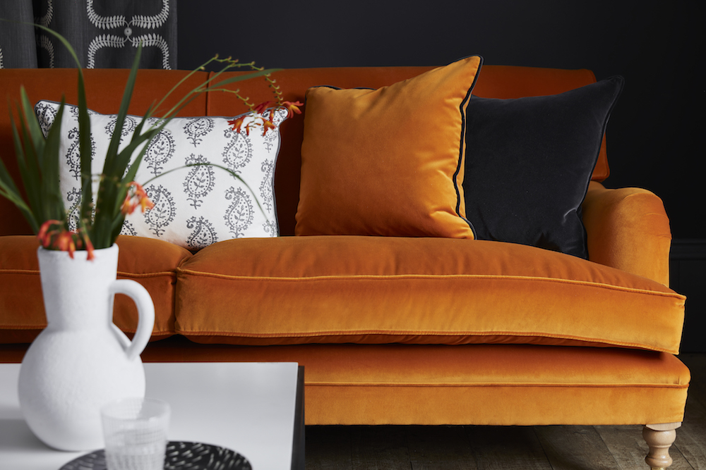 TRADITIONAL SOFA: Marigold Velvet VELVET-73 £58/mtr; CURTAIN: Up the Garden Path Winter PATH-50 £52/mtr; CUSHION (left): Large rectangular Life and Eternity Detail Charcoal LIFE-38 £49.50/mtr piped in Plain Linen Charcoal PLAIN-38 £48/mtr; CUSHION (middle): Marigold Velvet VELVET- 73 £58/mtr piped in Thunder Velvet VELVET-74 £58/mtr; CUSHION (right): Self piped and zipped Thunder Velvet VELVET-74 £58/mtr; RUG: Stripe and Dash Smoke, Cornflower RSD-30-16 £390; PAINT: Lamp Black 228 by Little Green Paint Company £42 per 2.5 ltr
