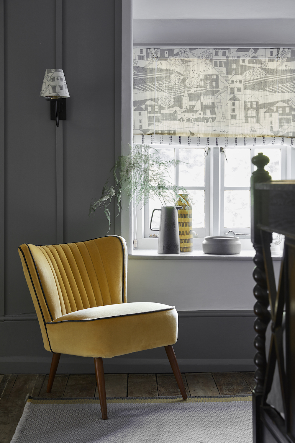 SWEDISH BLIND: By the Sea Scree, Charcoal SEA-67-38 £52/mtr lined in Simple Ticking Detail Charcoal TICKING-38 £49.50/mtr; LAMPSHADE: By the Sea Scree, Charcoal SEA-67-38 £52/mtr; RETRO CHAIR: Honey Velvet VELVET-72 £58/mtr piped in Thunder Velvet VELVET-74 £58/mtr; RUG: Geometric Grey, Saffron, Winter RGEO-95-52-50 £240