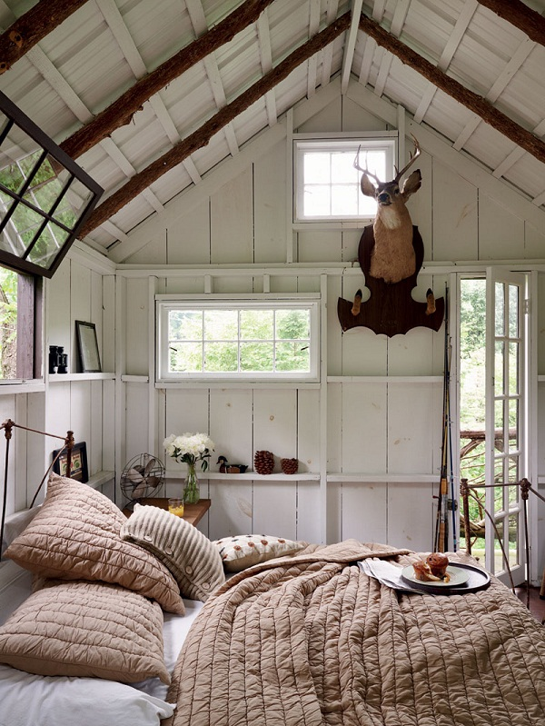 A treetop bedroom, complete with ornate iron bed, luxurious throws and chunky knit cushions.