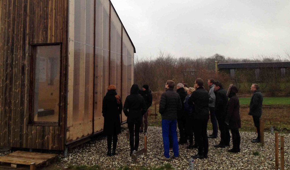 Deltagerne besigtiger Det Biologiske Hus, som er bygget af genbrugsmaterialer