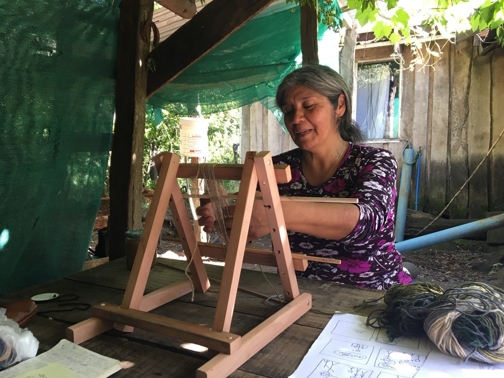 Pati testing a small scale Mapuche-inspired learning loom, designed for easy storage