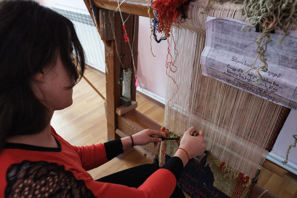 Qristine demonstrating how to carpet weave.