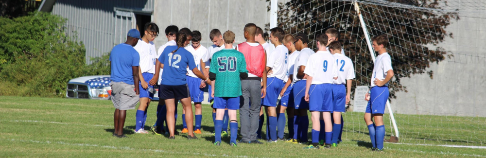 2016 Boy Varsity Soccer team huddles during half-time