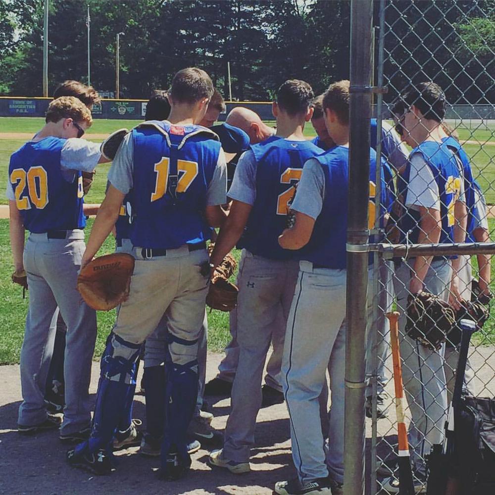 Boys Varsity Baseball team prays together before the Section 9 Championship.