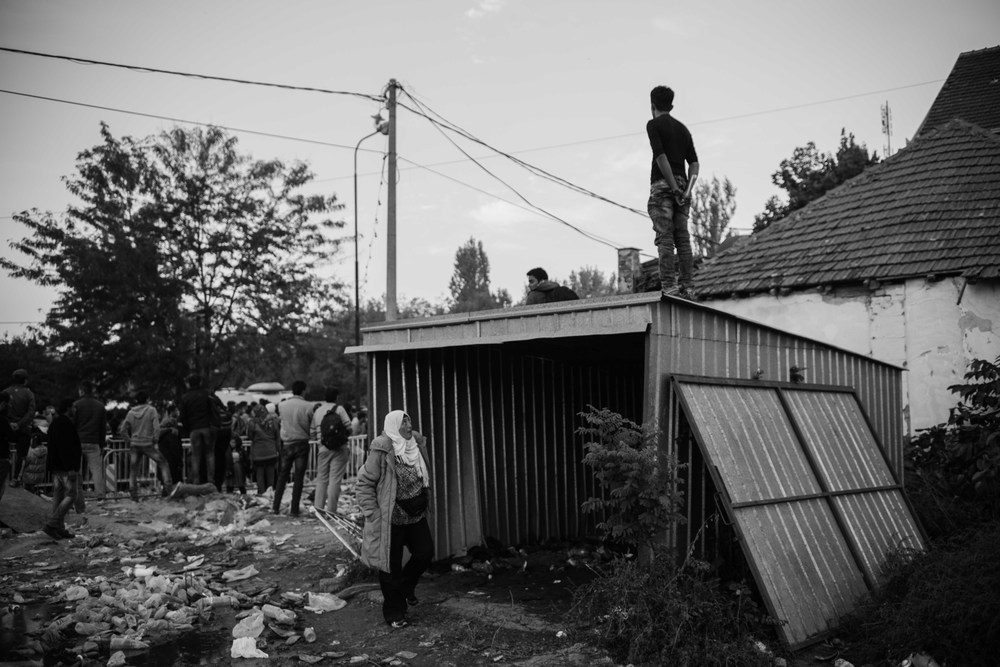 Daily life in Preševo, Serbia. A refugee stands upon a shed to watch a crowd that swells in frustration over prolonged documentation times.