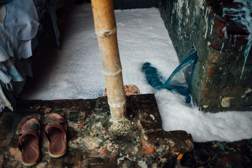 The bleaching process that the hides undergo taints the waste water a distinctive blue colour. The water containing toxic compounds runs through open sewers where it mixes with human waste, and animal fat left over from disposed carcasses. The majority of drains and open sewers in the area run blue with the bleaching compounds. The Buriganga itself runs either a blue or red colour near the exits of these pipes transporting the waste water.
