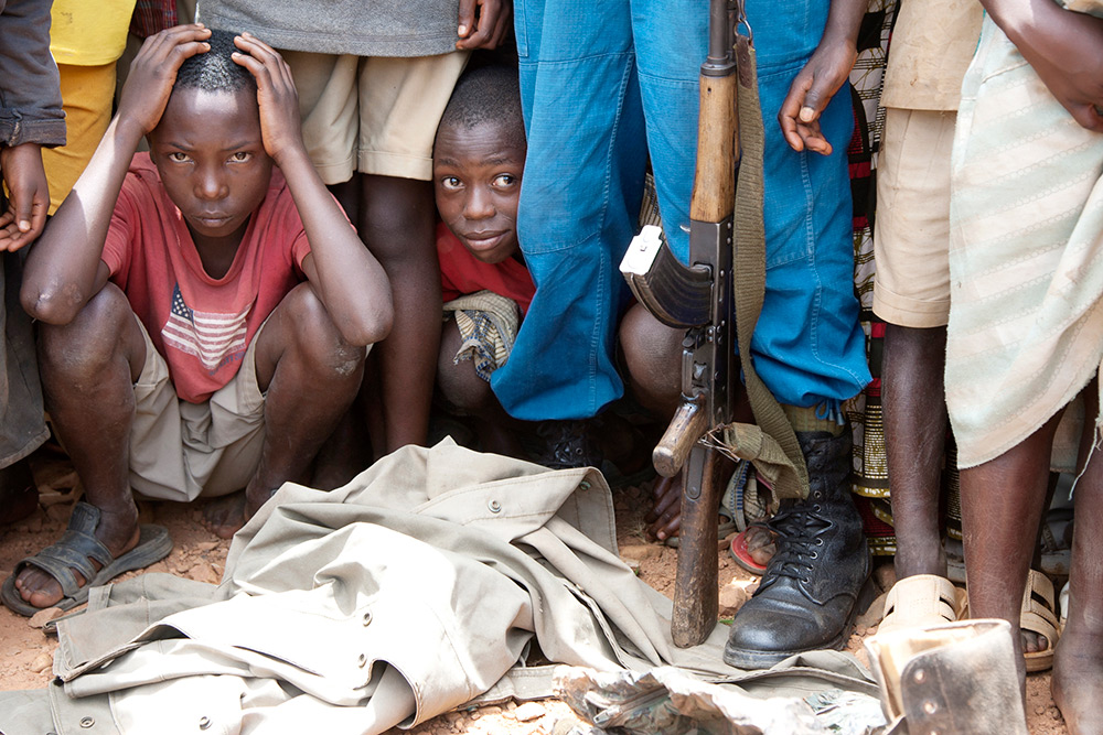 Children watch as weapons are turned in to officials in Burundi, where a 12-year civil war left much of the country with chronic food shortages. (Howard G. Buffett)