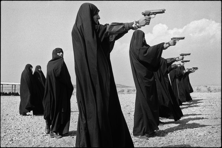 Photo by Jean Gaumy. IRAN. Tehran. 1986. Veiled women practice shooting on the outskirts of the city.