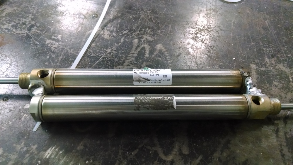 The welded pneumatic cylinders. Surprising lightweight- they weigh less that 2 lbs combined. Notice how they actuate in opposite directions to gain double the lift of a single cylinder.