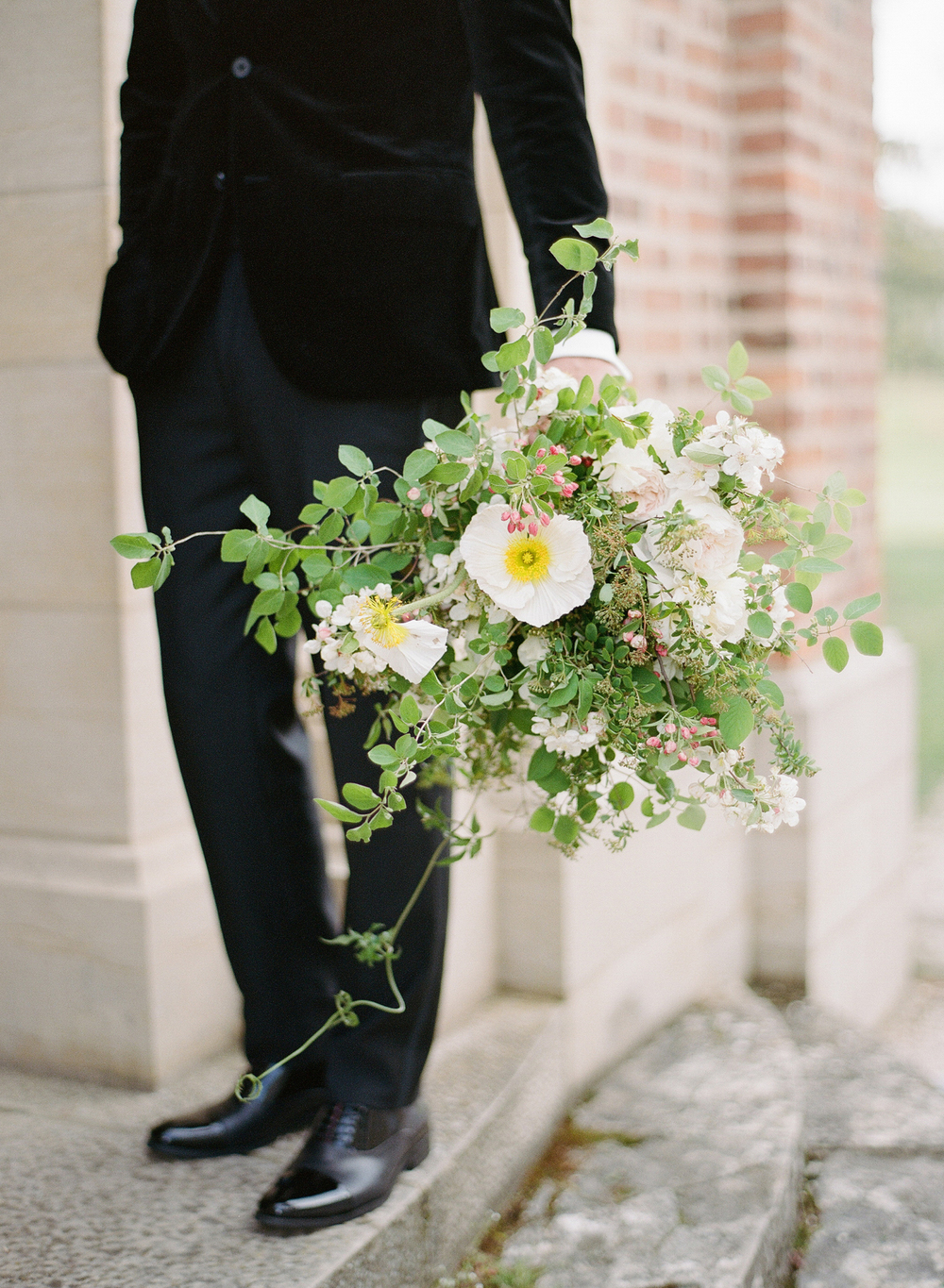 The groom, dressed in a black velvet jacket, holds his bride's rustic bouquet outside the chapel; photo by Sylvie Gil