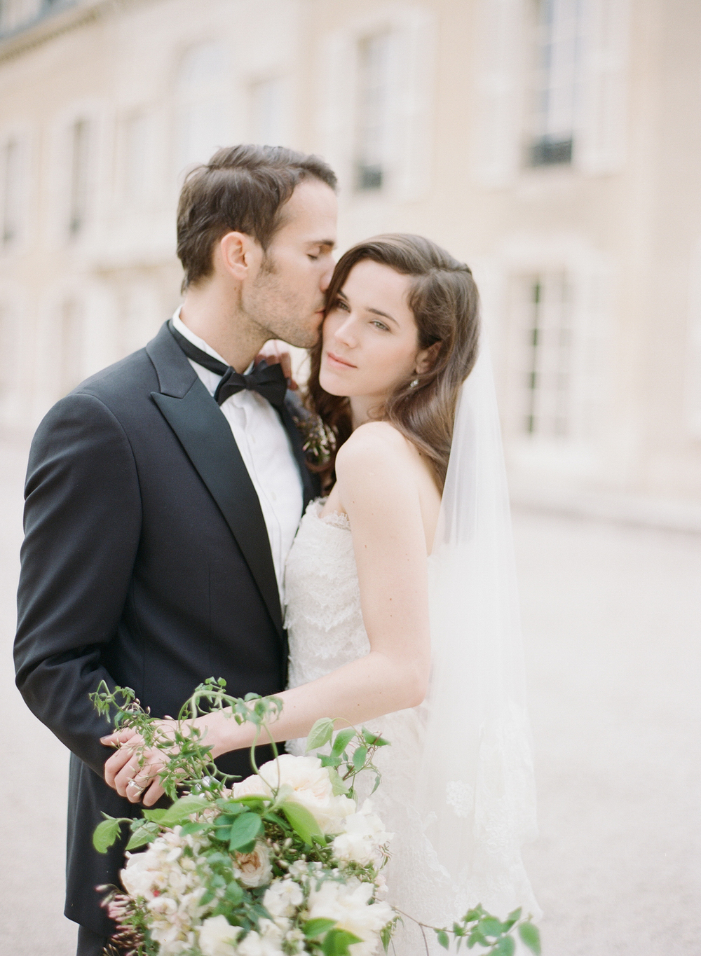 The groom kisses his bride on the cheek as they stand outside the Burgundy chateau; photo by Sylvie Gil