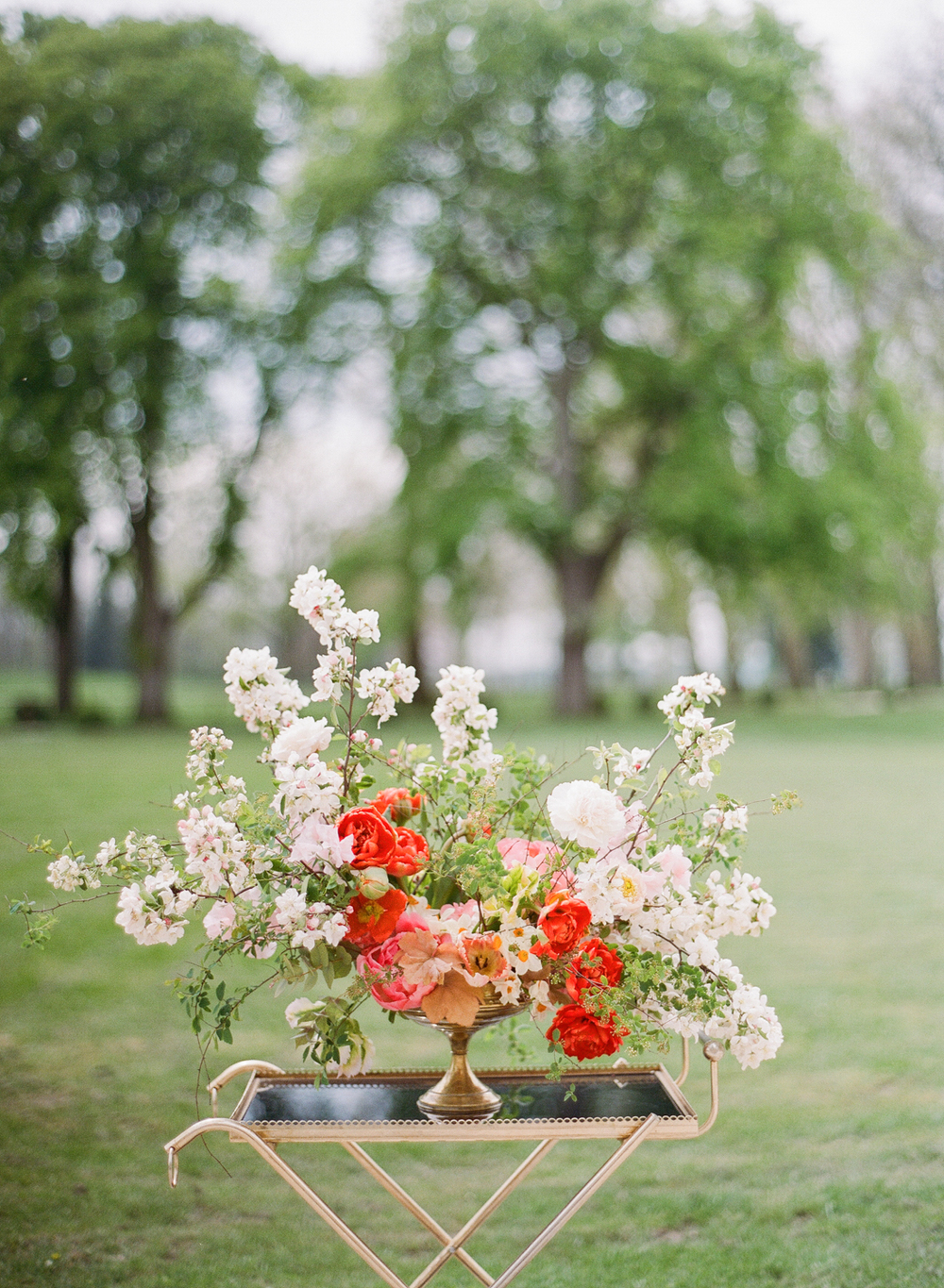 A tarnished gold vase holds an overflowing bouquet of reds and pastel pinks, set atop a gilt vintage tray; photo by Sylvie Gil