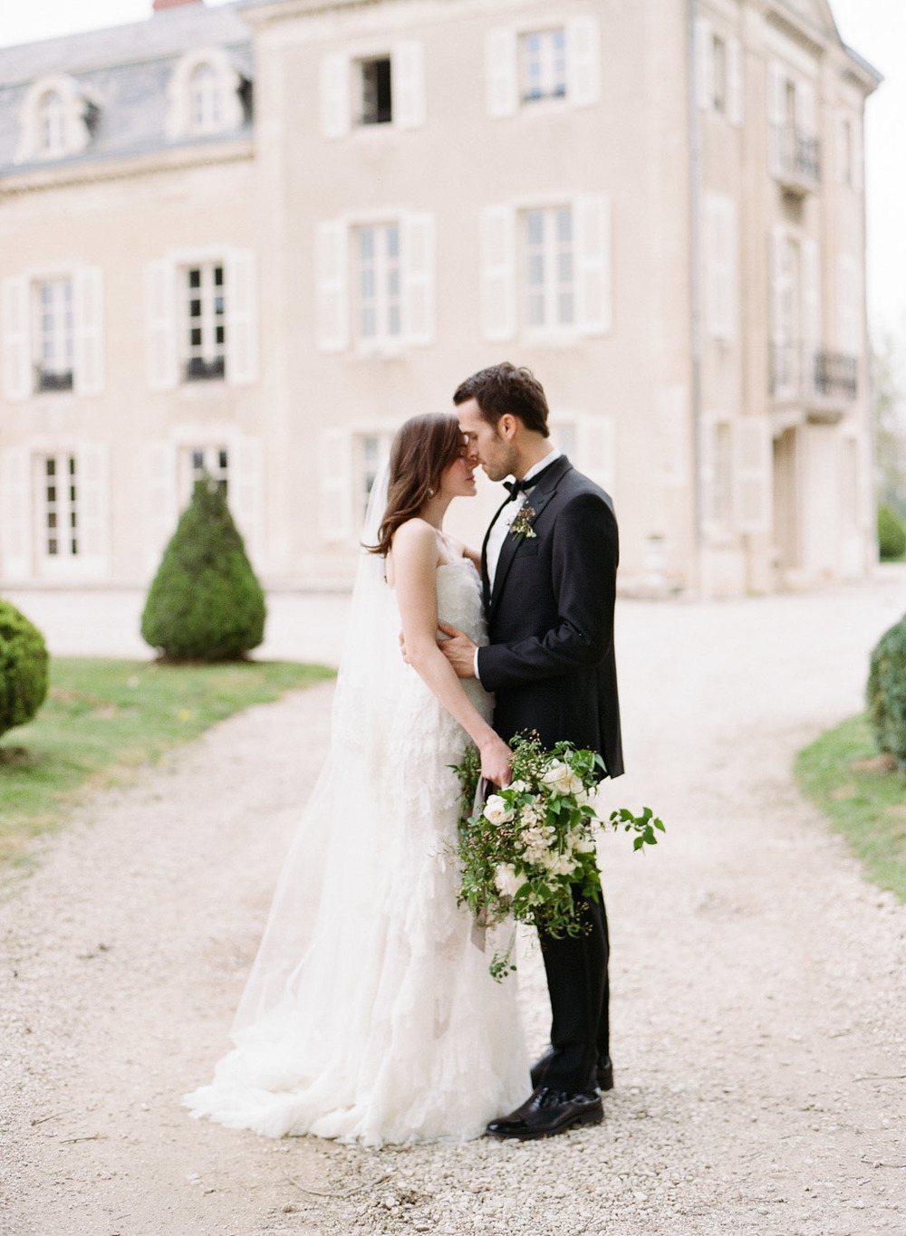 The groom holds his bride, dressed in a fluttery Oscar de la Renta gown, close, outside the chateau in Burgundy; photo by Sylvie Gil