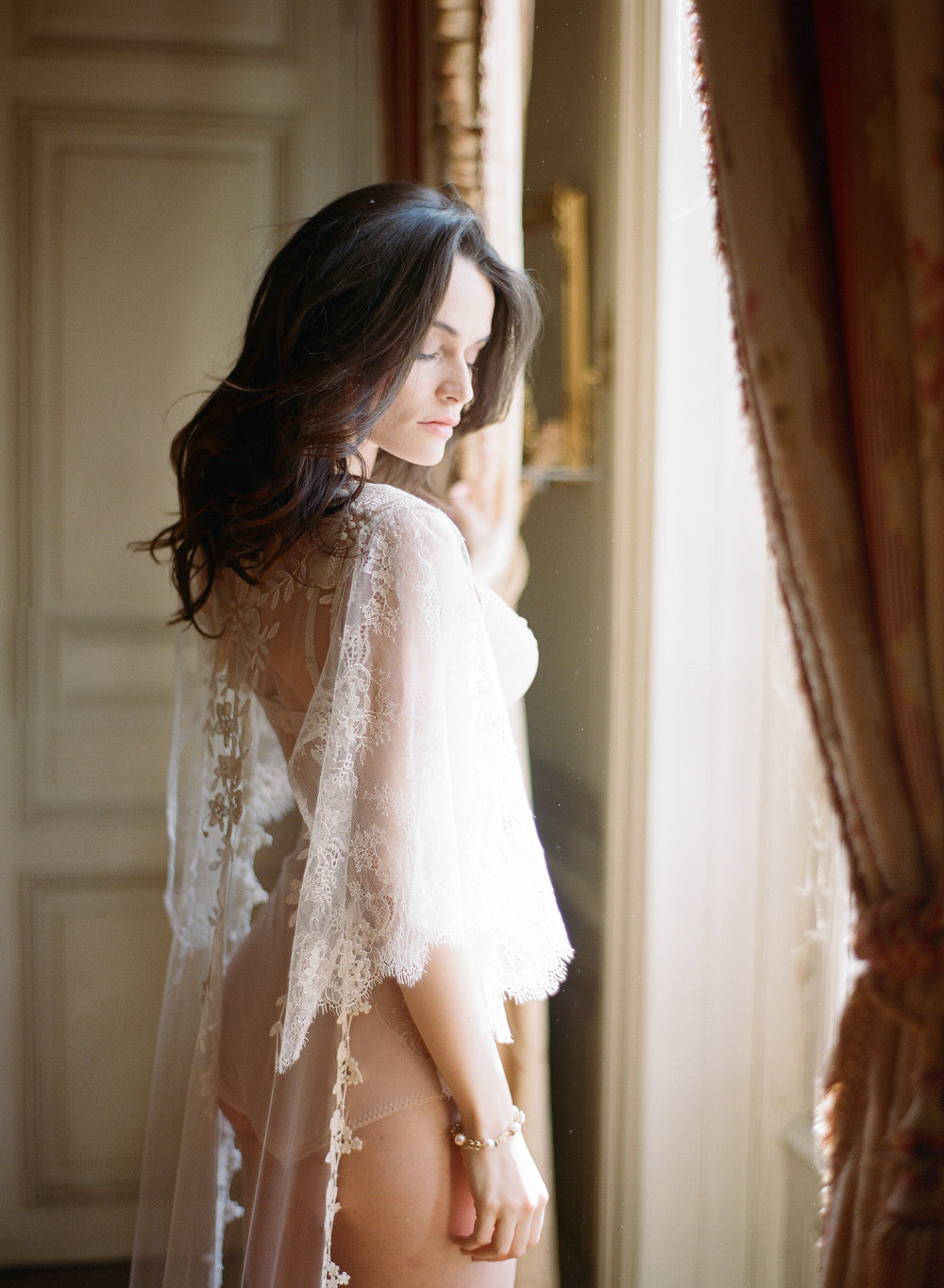 Bride in lingerie at the window in Chateau de Varennes; Sylvie Gil Photography