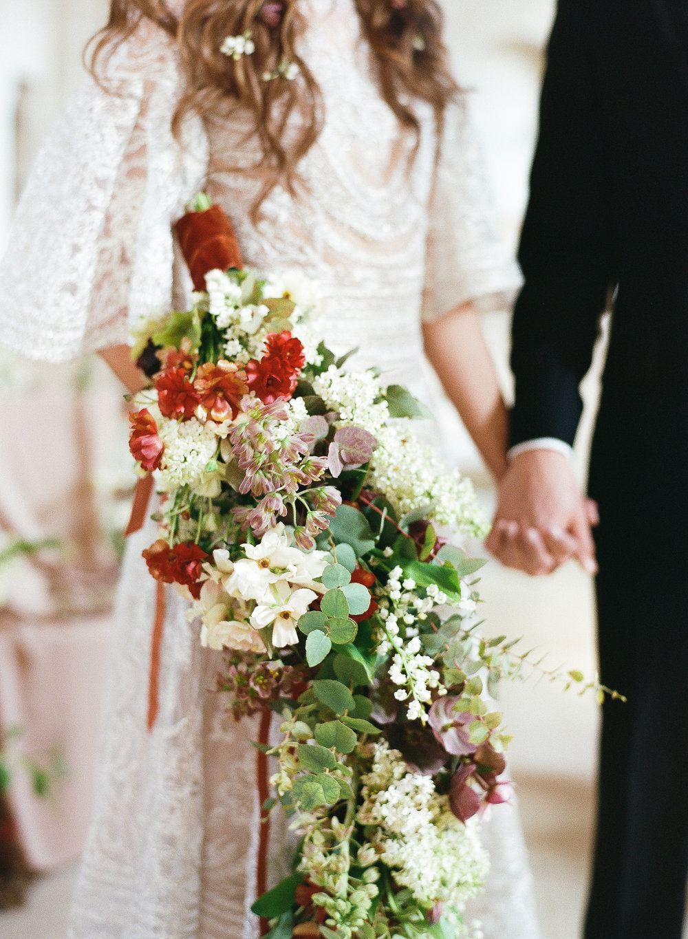 A cascading bouquet of cream and burgundy florals; Sylvie Gil Photography