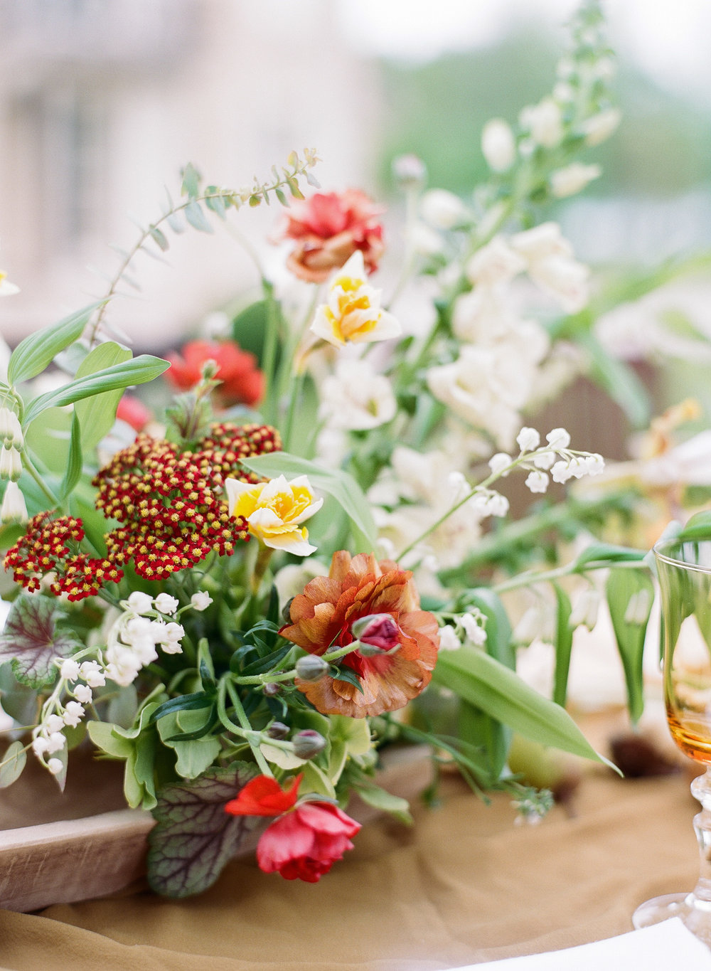 Burgundy and mustard florals decorate a wedding reception table at Chateau de Varennes in Burgundy, France; Sylvie Gil Photography