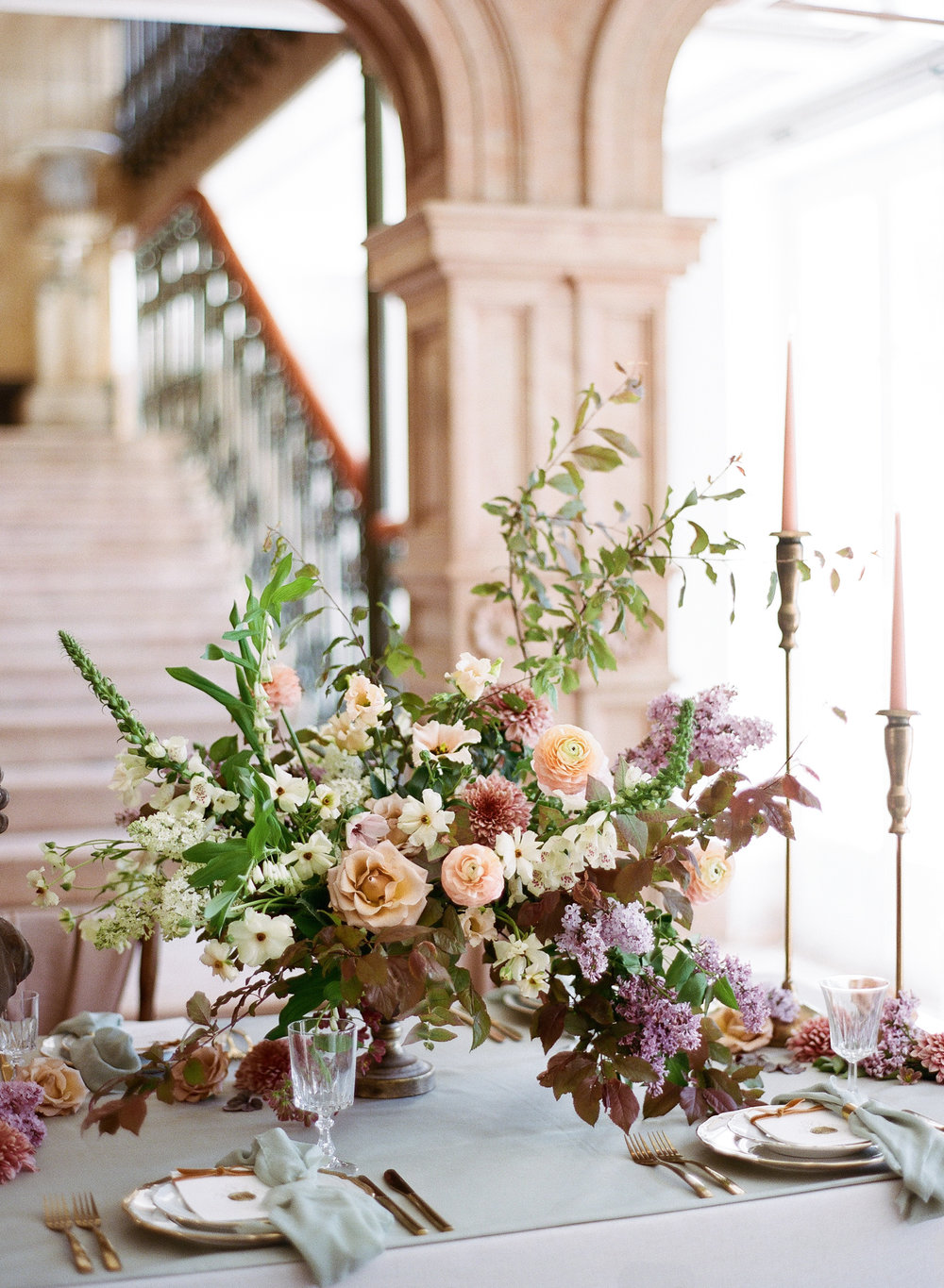 A sprawling bouquet of lavender, blush, and cream florals decorates a wedding reception table; Sylvie Gil Photography