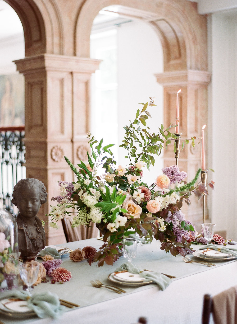 A wedding reception table at Chateau de Varennes, decorated with a sculpture bust and bell jar florals; Sylvie Gil Photography