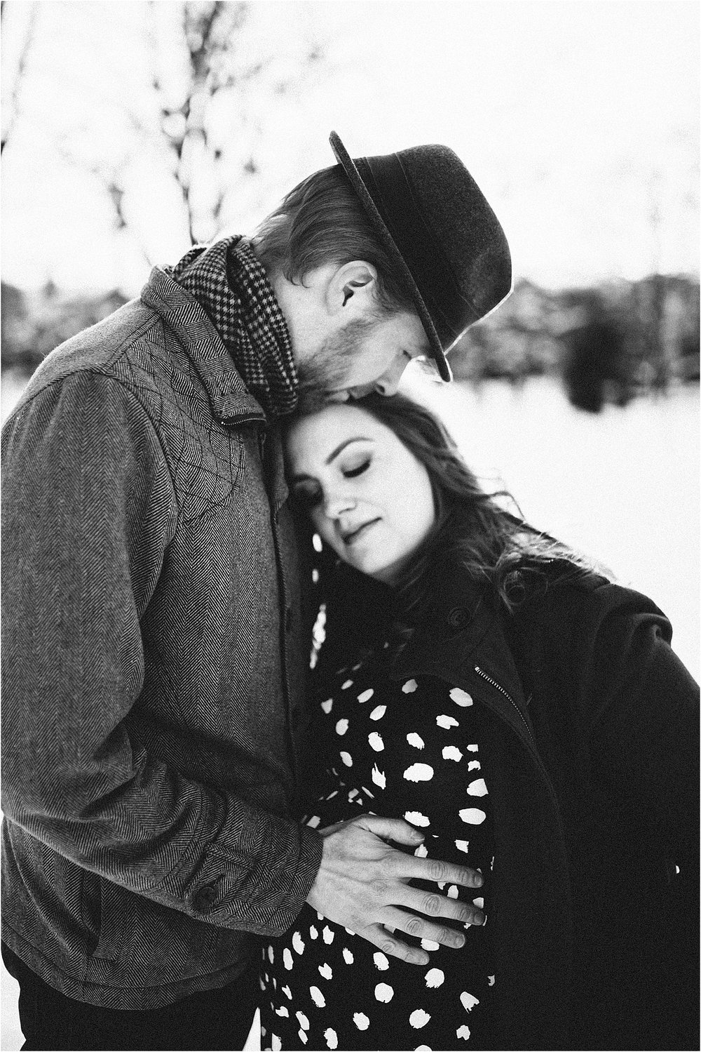 Black and white photo of pregnant mama with her husband kissing her forehead