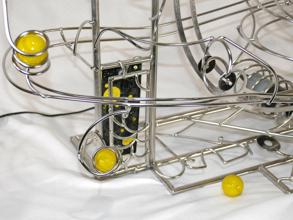 Rolling ball marble machine - close up of yellow marble detail