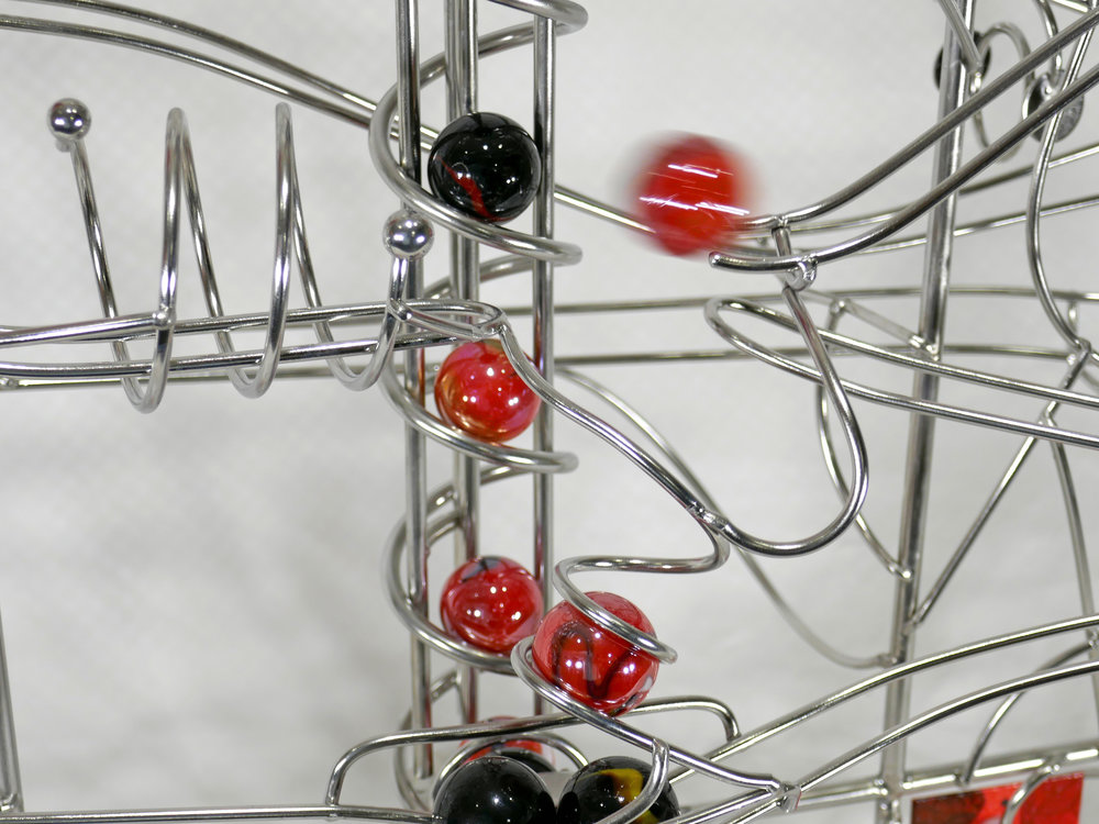 Rolling ball marble machines - action shot showing marbles travelling along the rails