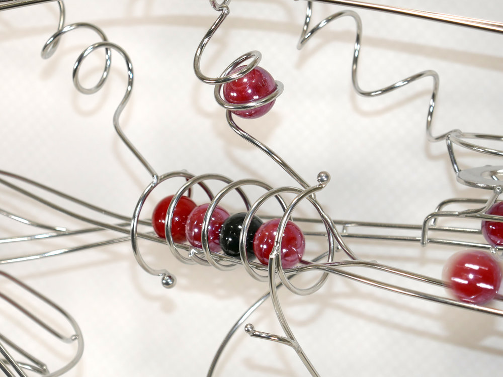 Rolling ball marble machine - close up of energy transfer kinetic element with red and black marbles