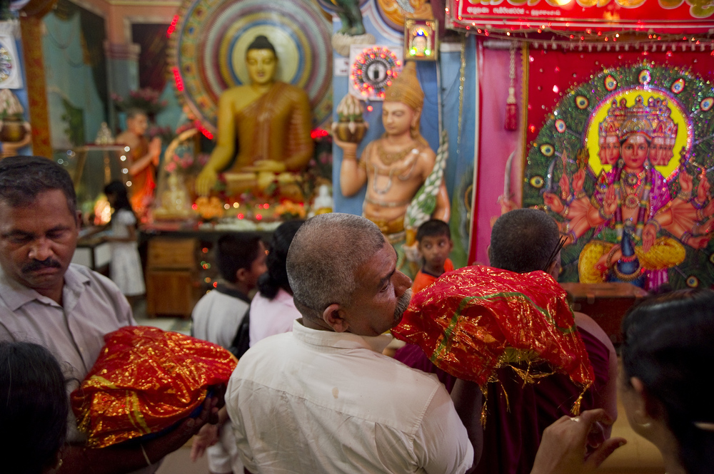 Pilgrims with offerings in Kataragama, Sri Lanka simultaneously worship Buddha and Lord Murugan, a Hindu god. The temple town is a regionally popular place of pilgrimage of Hindu, Buddhist, Muslim and indigenous Vedda communities of Sri Lanka and South India, where the god Muruga is the main deity.