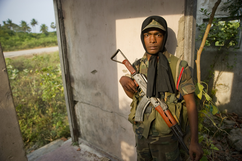 On the northern face of the Jaffna peninsula, near the now-deceased Tamil Tiger leader Velupilai Prabhakharan's house, a young Sri Lankan soldier guards one of many war-destroyed houses, now converted into makeshift guard shacks. With the conflict over, such outposts can be seen every 200 meters along the few roads that the public are allowed to travel along.