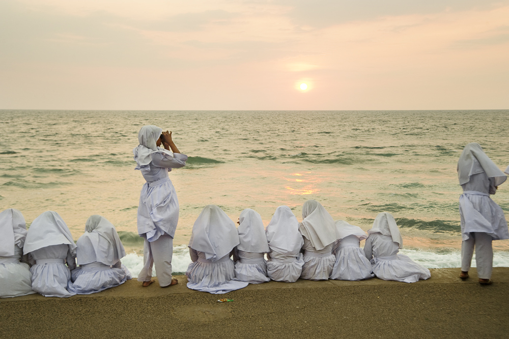 Schoolgirls in Colombo take in a sunset, looking across the Palk strait to India.