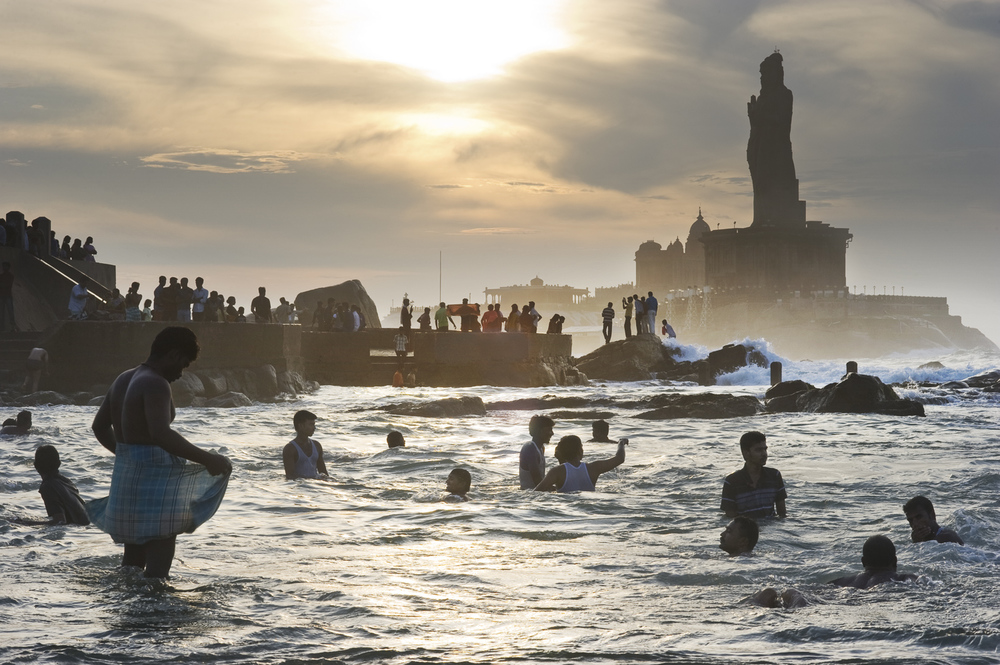"""Indian pilgrims visiting Kanyakumari, India's southernmost tip, take a holy dip at sunrise. The site's holiness is compounded by a major island-shrine to Swami Vivekananda, 'the maker of modern India;' the statue of Thiruvallur, the Tamil's poet-philosopher; and a key temple for the Hindu faith. As one pilgrim explained to me, """"How can we pay our respects to Mother India, if we do not come to this point to touch her feet?"""""""