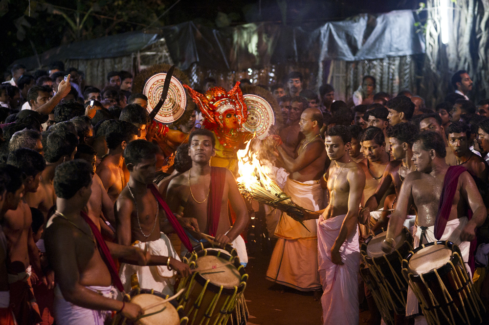 On the first of a 3-night performance, a theyyam performer enters the shrine, flanked by hordes of devotees.