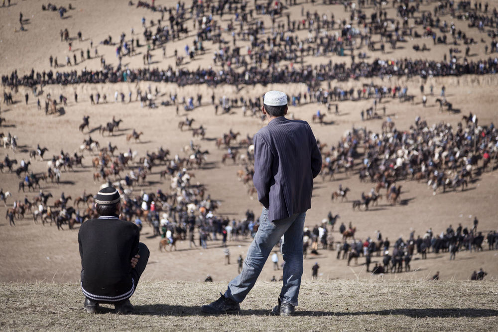 Young spectators view a horde of buzkashi horses from a nearby hill in Dangara, southern Tajikistan.