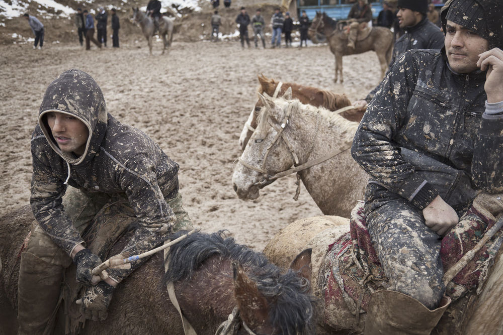 Tired buzkashi playing youths take rest during a muddy match. Popular throughout much of Central Asia, buzkashi is a form of horse polo in which horseback players wrestle a goat carcass across a playing field.