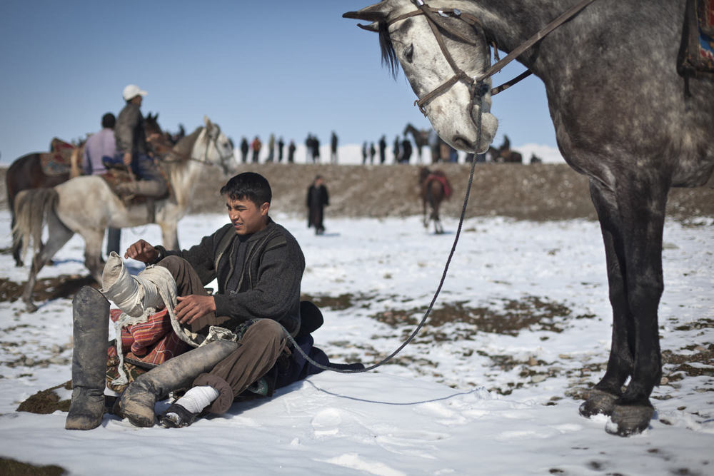 A player puts on his boots before a match near Dushanbe.