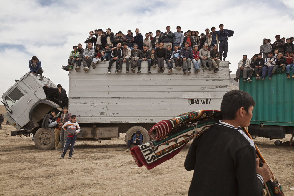 Spectators look on from a high perch on top of trucks, as a chovandoz assistant carries away a carpet won as a prize during the match in Hisor, western Tajikistan.