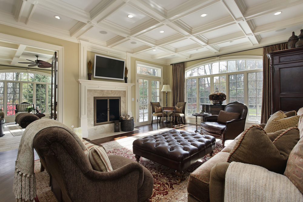Custom ideas for decorating a family room include providing a comfortable seating area with room for conversation and TV-watching. Here, you can see the custom mill work, leather furniture, custom fireplace, and custom coffered ceiling that anchor the room and make it a center of the house.